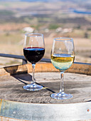 Glasses of red wine and white wine on a wooden barrel (Alentejo, Portugal)