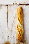 A fresh baguette on a white wooden background (top view)