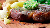 Beef steak with melting herb butter and potatoes on a wooden board