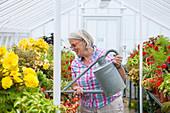 Frau gießt Blumen im Gewächshaus