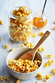 Popcorn with curry and salt in a bowl and a jar