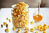 Popcorn with curry and salt in a jar next to a small jar of curry powder