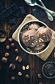Chocolate and hazelnut ice cream in a silver bowl with chopped nuts