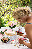 A summer table laid with redcurrant cakes and desserts