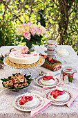 A table laid in a garden with redcurrant cake and desserts