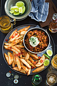 Hot beef and beer chilli with crunchy potato wedges with chilli and lime salt