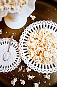 Antique white plates and dishes with popcorn and sea salt on a gold tables