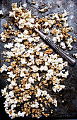 Popcorn as a healthy snack - popcorn, granola and sliced almonds drizzled with manuka honey on an antique baking sheet