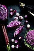 Verschiedene lila Gemüsesorten auf schwarzer Schieferplatte