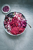Mixed salad made with radicchio, grated beetroot, beetroot shoots, pomegranate seeds, red batavia lettuce, red cabbage and purple chicory with a bowl of beetroot salt