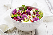 Mixed leaf salad with purple cauliflower, avocado and pomegranate seeds