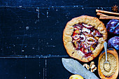 Homemade wholegrain plum pie or tart with walnuts and fresh plums on vintage wooden background