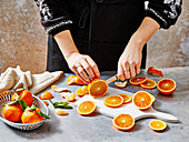A woman slicing blood oranges