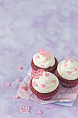 Red velvet cupcakes with cream cheese and pink sugar hearts