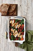 Hühnerbrust mit Paranusskruste auf gerösteten Tomaten und Spinat (Aufsicht)
