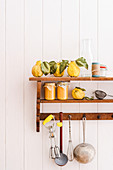 Quince purée, fresh quinces and kitchen utensils on a wall shelf