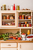 Preserves, fresh fruit and vegetables on a kitchen dresser