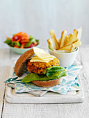 A bean burger with chips and salad