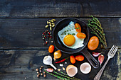 Fresh vegetables with fried eggs on dark wooden background with space for text