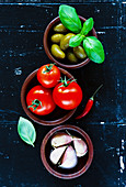 Wooden bowls with green olives, cherry tomatoes and garlic on dark vintage background