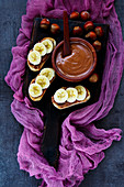 Old wooden serving board with delicious sweet hazelnut and chocolate spread sandwiches with sliced bananas for tasty breakfast