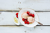 Bowl of organic melting raspberry ice-cream with fresh berries and white chocolate on wooden background