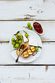 Tasty breakfast set on white wooden table. Brie cheese and fig jam sandwiches with fresh grapes over rustic background