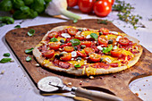 Vegetable pizza with tomatoes, chilli and capers on a pizza paddle