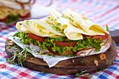Krustenbrotscheibe belegt mit Gouda, Gurken, Tomaten und Salat