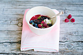Raspberry and chia seed pudding with blueberry compote, raspberry sauce, fresh blueberries, raspberries and mint