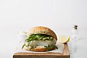 Fischburger mit Gurken und Dill auf Holzschneidebrett
