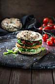 Sesambagel mit Kichererbsen-Zucchini-Puffer, eingelegten Tomaten, Salat und Gurke (vegan)