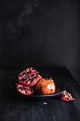 Granatapfel, ganz und aufgeschnitten, in einer Schale