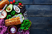 Delicious Vegetarian Sandwich (with Avocado, Tomato, Onion, Cream Cheese, Herbs and Spices) on dark rustic background