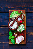 Delicious Sandwiches with avocado, radish, sprouts, cream cheese, herbs and spices, wholegrain bun on rustic wooden board