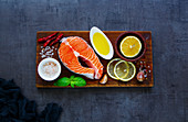 Delicious uncooked salmon fish steak with lemon, oil, herbs and spices on rustic wooden chopping board over dark concrete background