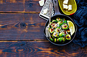 Old cast iron pan of roasted brussels sprouts with cheese parmesan on wooden rustic background