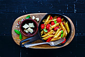 Italian dinner on black rustic wood background. Pasta penne with roasted tomatoes, basil and parmesan cheese