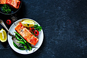 Roasted salmon with poached green peas, tomatoes, lemon in plate and salmon fillet in vintage frying pan