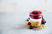 Detox breakfast in jar. Greek yogurt, granola, fresh berry breakfast, white wooden wall background