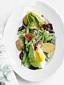 Nicoise salad with potatoes, dried tomatoes, green beans and egg