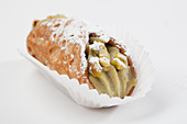 A sweet cannelloni filled with pistachio cream, in a paper case