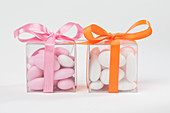 Pink and white sugared almonds in plastic boxes