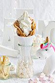 A bubble waffle with frozen yoghurt next to a unicorn decoration