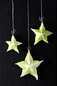 Aufgeschnittene Sternfrucht auf Tafel mit gemalter Aufhängung als Weihnachtsschmuck