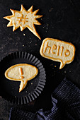 Three comic-style speech bubble biscuits with golden sugar writing