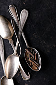 Five silver spoons with pepper on a dark background