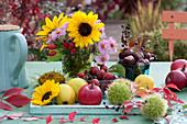 Herbstliches Tischarrangement aus Früchten und Blüten