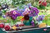 Herbst-Arrangement mit kleinen Aster - Sträußen und Früchten