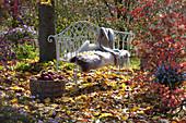 Gartenbank mit Fell und Decke unterm Baum